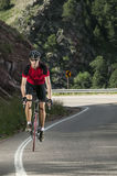 Fit male bicyclist wearing red jersey riding mountain road. Stock Photography