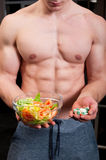 Fit male chosing between pills and natural salad Royalty Free Stock Photo