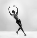 A fit male dancer posing on a grey background Royalty Free Stock Images