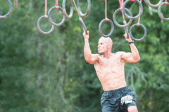 Fit Male Grasps Rings In Extreme Obstacle Course Race. Conyers, GA, USA - August 22, 2015:  A young fit male swings from rings suspended from wood beams to keep Stock Photos