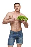 Fit male holding vegetables and showing thumbs up Stock Photo