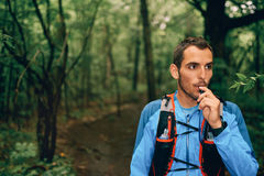 Fit male jogger hydrates while day training for cross country forest trail race in a nature park. Portait of a competitive, athletic millennial man drinking Royalty Free Stock Photography