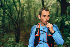 Fit male jogger hydrates while day training for cross country forest trail race in a nature park. Portait of a competitive, athletic millennial man drinking Royalty Free Stock Images