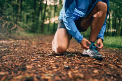 Fit male jogger ties shoes while day training for cross country forest trail race in a nature park. Stock Photography