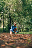 Fit male jogger ties shoes while day training for cross country forest trail race in a nature park. Royalty Free Stock Image