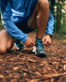 Fit male jogger ties shoes while day training for cross country forest trail race in a nature park. Royalty Free Stock Photography