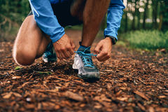 Fit male jogger ties shoes while day training for cross country forest trail race in a nature park. Stock Photos