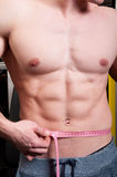 Fit male measuring his waist. Fit male or body builder measuring his waist using a pink meter Stock Photo