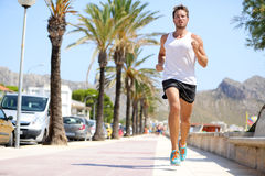 Fit male runner running outside on boardwalk. Young man model training fitness jogging on Mallorca beach city outdoors in summer sun. Palms in background Stock Image