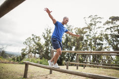 Fit man balancing on hurdles during obstacle course training. At boot camp Royalty Free Stock Photography