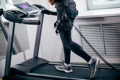 Man in electric muscle stimulation suit for ems training running on treadmill. Fit Man in black electric muscle stimulation suit for ems training running on Stock Images