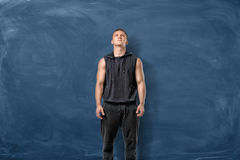 Fit man in black standing on blue chalkboard background and looking up. Fitness and health. Exercising. Sports challenges Stock Image