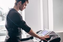 Man in black suit for ems training running on treadmill at gym. Fit Man in black suit for ems training preparing for running on treadmill at gym Royalty Free Stock Images