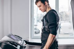 Man in black suit for ems training running on treadmill at gym. Fit Man in black suit for ems training preparing for running on treadmill at gym Royalty Free Stock Photo