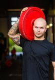 Fit Man Carrying Barbell Plate in Gym Royalty Free Stock Photography