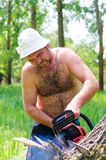 Fit man carrying a chainsaw in woodland Royalty Free Stock Photography