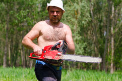 Fit man carrying a chainsaw in woodland Stock Images
