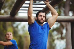 Fit man climbing monkey bars Stock Photo