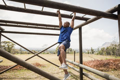 Fit man climbing monkey bars during obstacle course Royalty Free Stock Images