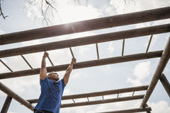 Fit man climbing monkey bars during obstacle course. In boot camp Royalty Free Stock Image