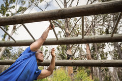 Fit man climbing monkey bars during obstacle course Royalty Free Stock Image