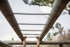 Fit man climbing monkey bars during obstacle course. In boot camp Royalty Free Stock Photo