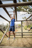 Fit man climbing monkey bars during obstacle course Stock Photography