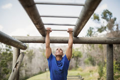 Fit man climbing monkey bars during obstacle course. In boot camp Stock Photos