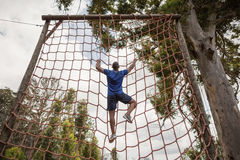 Fit man climbing a net during obstacle course. In boot camp Royalty Free Stock Images