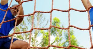 Fit man climbing a net during obstacle course 4k. Fit man climbing a net during obstacle course in boot camp 4k stock video