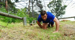 Fit man crawling under the net during obstacle course 4k. Fit man crawling under the net during obstacle course in boot camp 4k stock video
