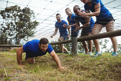 Fit man crawling under the net during obstacle course while fit people cheering Royalty Free Stock Images