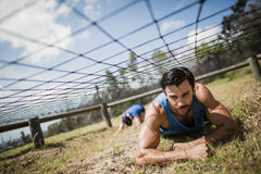 Fit man crawling under the net during obstacle course. Fit men crawling under the net during obstacle course in boot camp royalty free stock photo