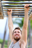 Fit man cross training outside on monkey bars. Fit man cross training on monkey bars station. Fitness workout on brachiation ladder in an outdoor gym outside Stock Images