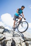 Fit man cycling on rocky terrain Royalty Free Stock Photography