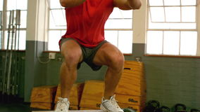 Fit man doing box jumps in gym