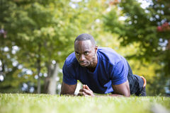Fit man doing plank core exercise in the park stock photography