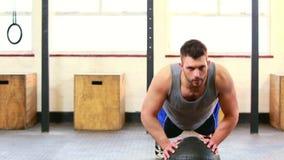 Fit man doing push ups in crossfit studio