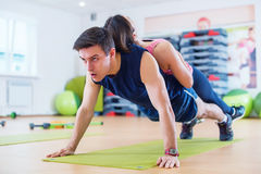 Fit man doing push-ups with woman on back in gym using own weight. Sport training arms, teamwork. Fit men doing push-ups with women on back in gym using own Stock Photos