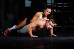 Fit man doing push-ups with woman on back in nature. Fit men doing push-ups with women on back. healthy couple, workout with own body weight, indoor lie , rest Stock Image