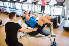 Fit man doing sit ups with trainer. Fit men doing sit ups with trainer at the gym Stock Image
