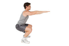 Fit man doing squats Stock Photos