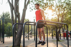Fit man doing triceps dips on parallel bars at park exercising outdoors Stock Images
