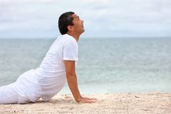 Fit man doing yoga at the beach Stock Images