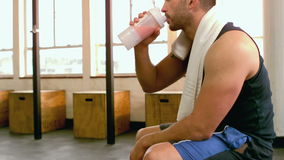 Fit man drinking protein shake in gym stock video footage