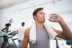 Fit man drinking water beside treadmills Royalty Free Stock Photo