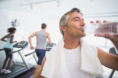Fit man drinking water beside treadmills Royalty Free Stock Images