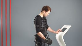 Fit man in Electrical Muscular Stimulation suit standing with dumbbells. Fit man in Electrical Muscular Stimulation suit standing with dumbbells stock video footage