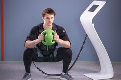 Man in electric muscular suit to stimulate with training medecine ball. Fit Man in EMS suit training with medecine ball Royalty Free Stock Image