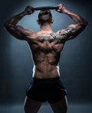 Fit Man with Exercise Bar on his Head in Rear View Stock Photography